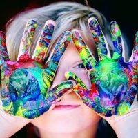 Copil cu maini pictate cu multe culori