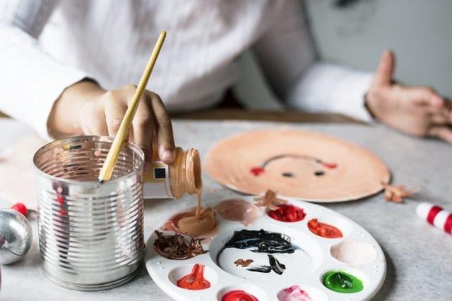 copil care picteaza cu pensula paleta de culori