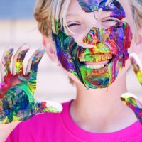 copil cu vopsea colorata pe maini
