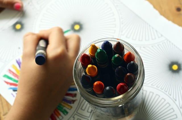 copil care deseneaza cu creioane colorate